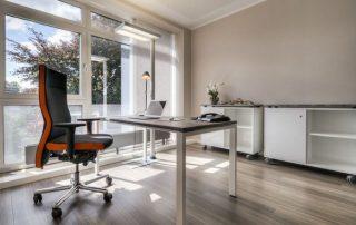 Schreibtisch höhenverstellbar mit schwebender Tischplatte, rollbare Flachstrecke für Ordner und verschließbarer Personalteil