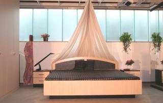 Doppelbett mit gerundetem Kopfteil und Einzelnachtschränke